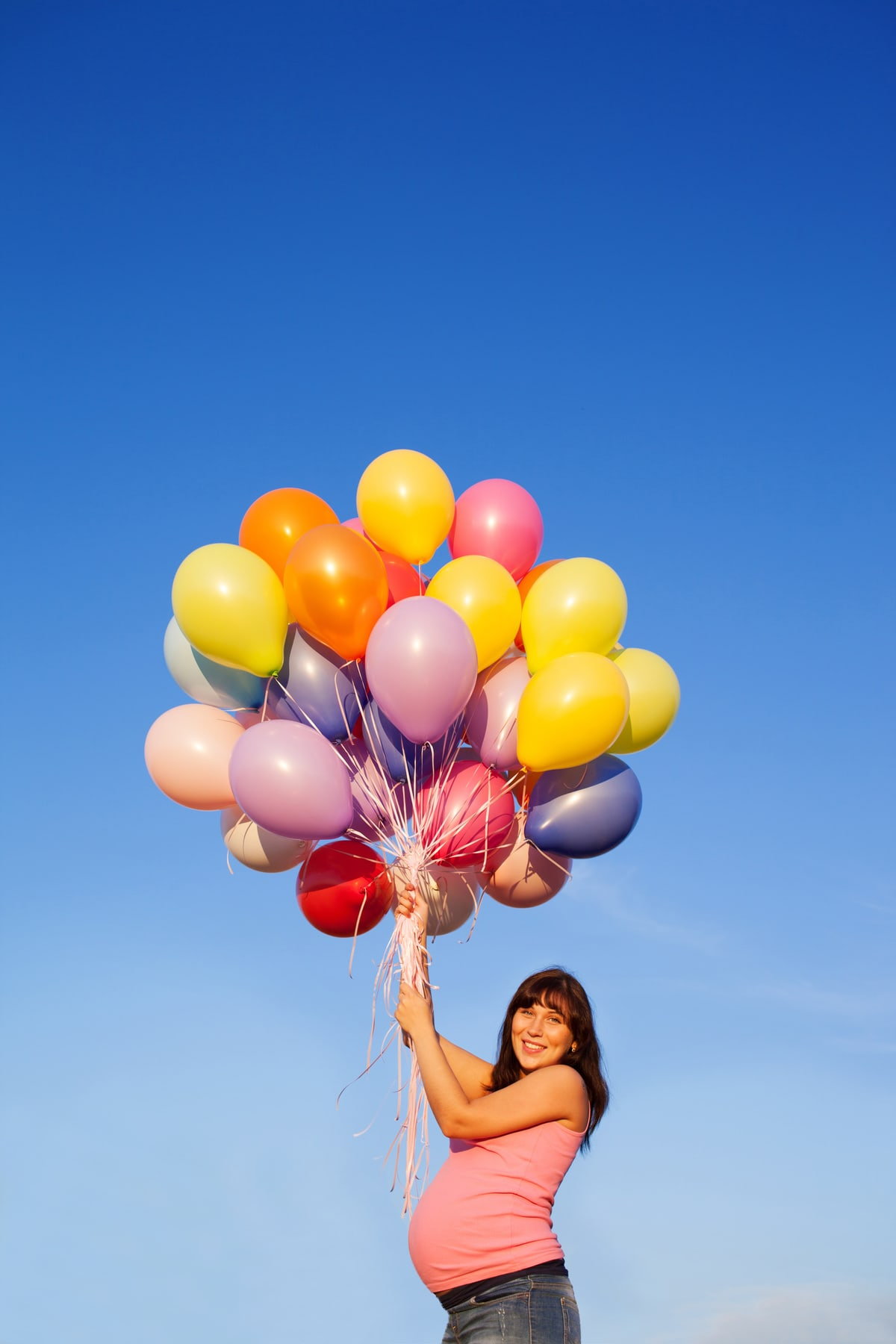Beautiful happy young pregnant woman girl outdoors with balloons on sky background with her hands up